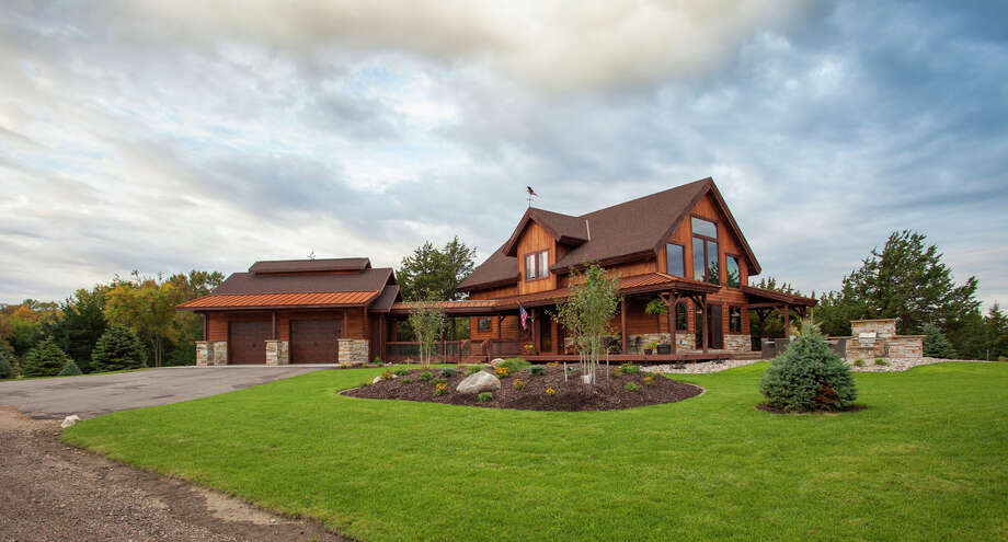 This barn home has open porches and is located on a lake. Photo: Courtesy/Sand Creek Post & Beam