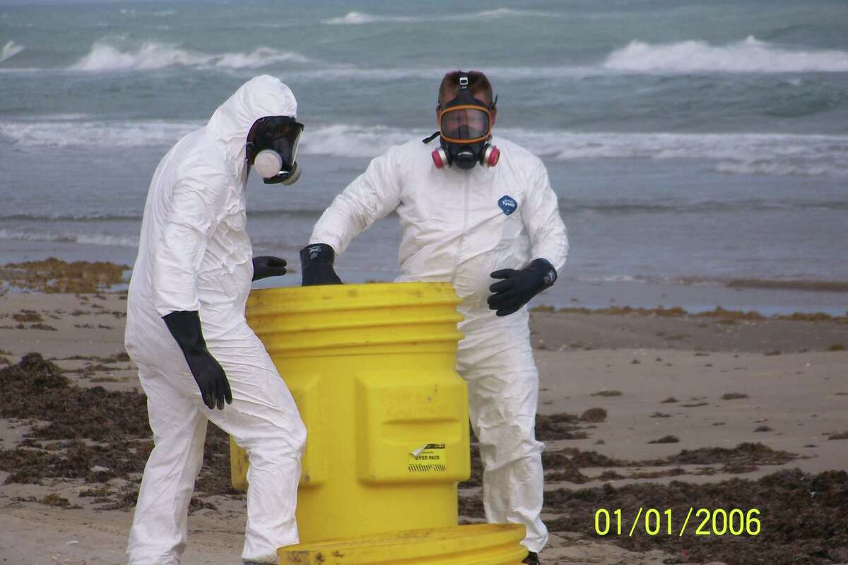 Workers in hazmat suits remove hazardous waste that washed up on Padre Island.