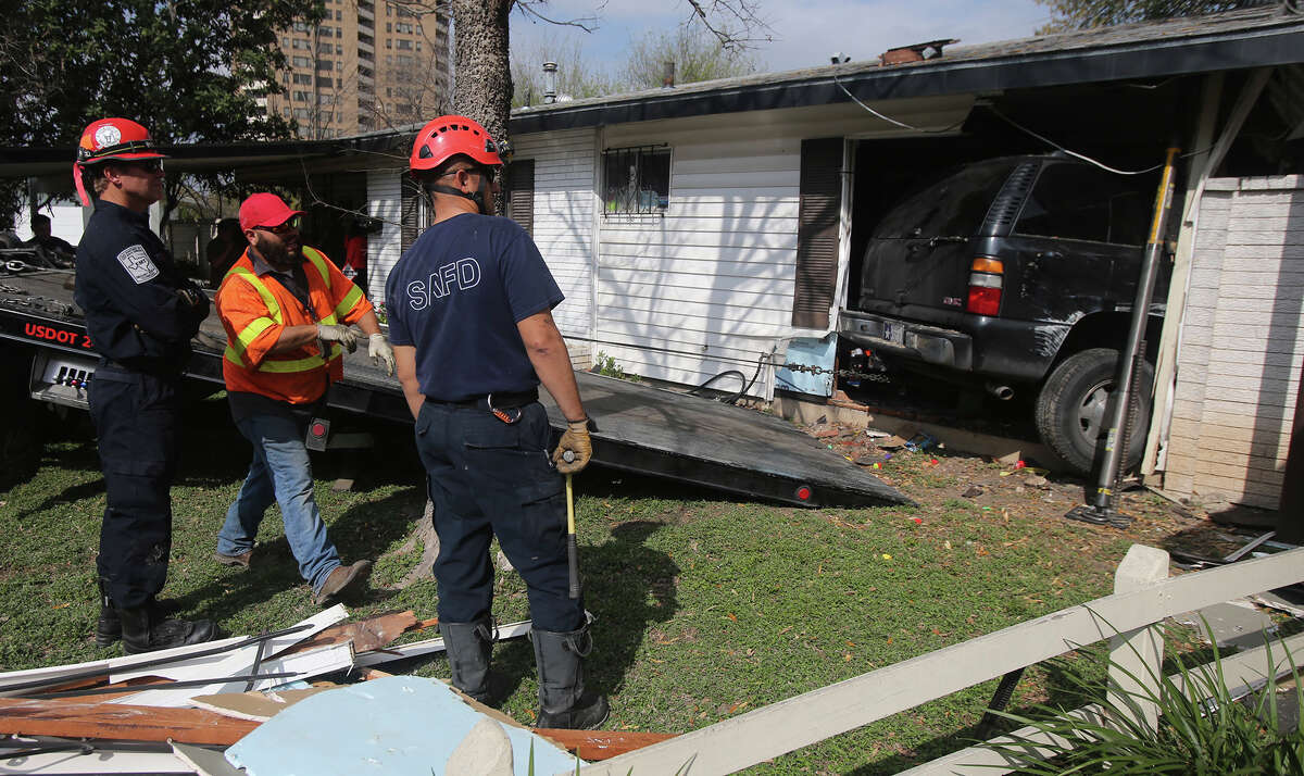 San Antonio firefighters work Wednesday March 2, 2016 to remove an SUV that crashed into a home around 2:15 p.m.. San Antonio police officer Andrew Montemayor said Leonard Castillo, Jr. was driving his GMC Yukon down the 7800 block of Northway when his brakes failed and he crashed into one of the home's bedrooms. Nobody in the home was injured and Castillo was not injured either.