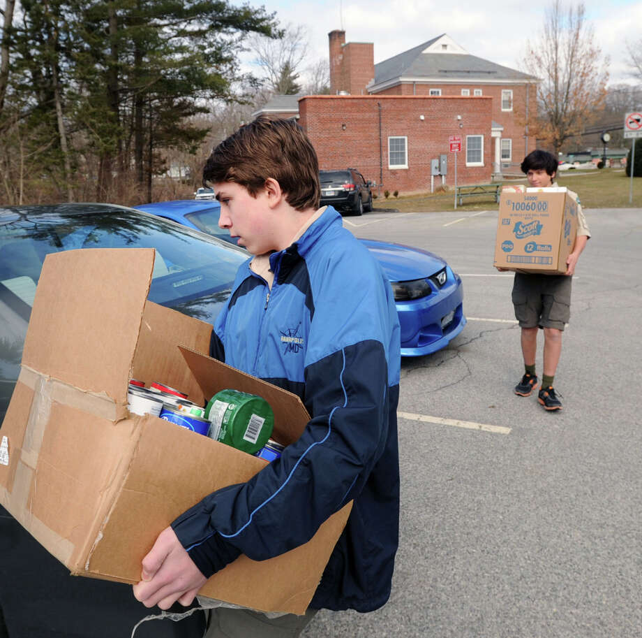 Boy Scouts Dylan DeChiara, left, and Dario Volterra of Troop 35 of Glenville, carry boxes of food their troop collected during the 2013 Greenwich Scouts' annual food drive for the Neighbor to Neighbor food pantry. This year's food drive is set for March 5. Photo: Bob Luckey / Bob Luckey / Greenwich Time