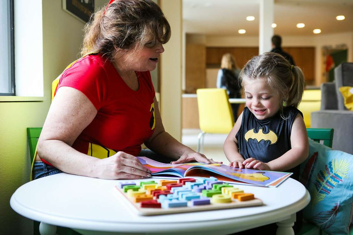 Patti Cunningham reads a book to her granddaughter Shiloh Lecours-Gary, 3, in the playroom of Family House, a free temporary housing facility for families of children who are sick, in San Francisco, California, on Wednesday, March 2, 2016. Shiloh was born prematurely in 2012 and her family stayed in Family House for over three months.