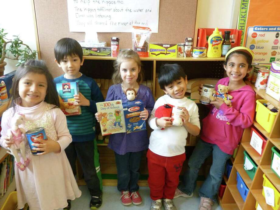 International School at Dundee kindergarteners (from left) Loraine Vargas, Dario Abbate, Eve Woodward, Cebastian Guico and Kareena Kumar donate books, food and toys to Greenwichís Neighbor to Neighbor in celebration of their 100th day of elementary school. Each year, the schoolís three kindergarten classes each collect 100 food donations for the local charity, in celebration of the 100th day milestone and in connection with their International Baccalaureate ìCaringî Learner Profile, which emphasizes care for community and neighbors. Photo: Contributed / Contributed Photo / Greenwich Time Contributed