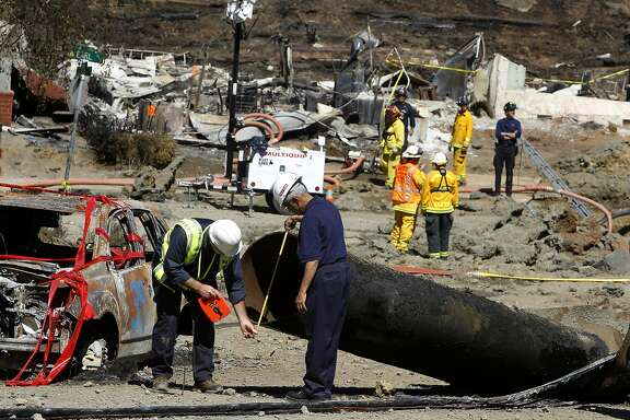 Federal investigators inspect a 40-foot section of pipeline on Glenview Drive in San Bruno on Saturday.