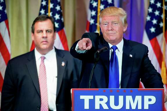 Republican presidential candidate Donald Trump, accompanied by New Jersey Gov. Chris Christie, left, takes questions from members of the media during a news conference on Super Tuesday primary election night in the White and Gold Ballroom at The Mar-A-Lago Club in Palm Beach, Fla., Tuesday, March 1, 2016. (AP Photo/Andrew Harnik)