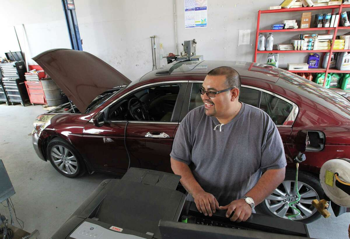 Johnny Pulido, a state vehicle inspector, talks to a coworker while performing an inspection Wednesday, March 2, 2016, in Houston. Texas moved to a single-sticker system for vehicle registrations and inspections a year ago.