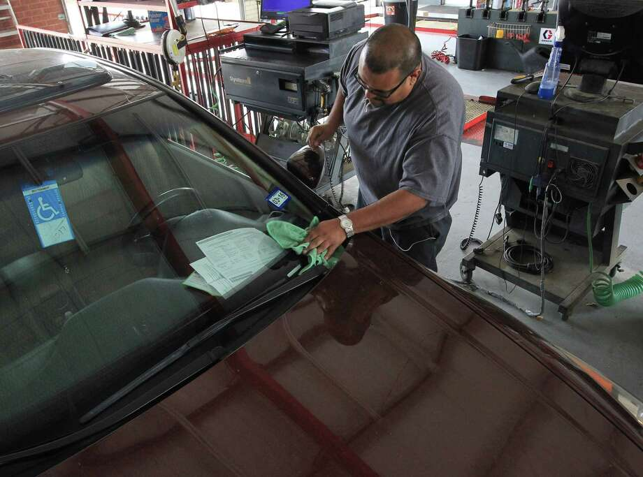 Johnny Pulido, a state vehicle inspector, removes two expired stickers on March 2. The Texas Department of Motor ...