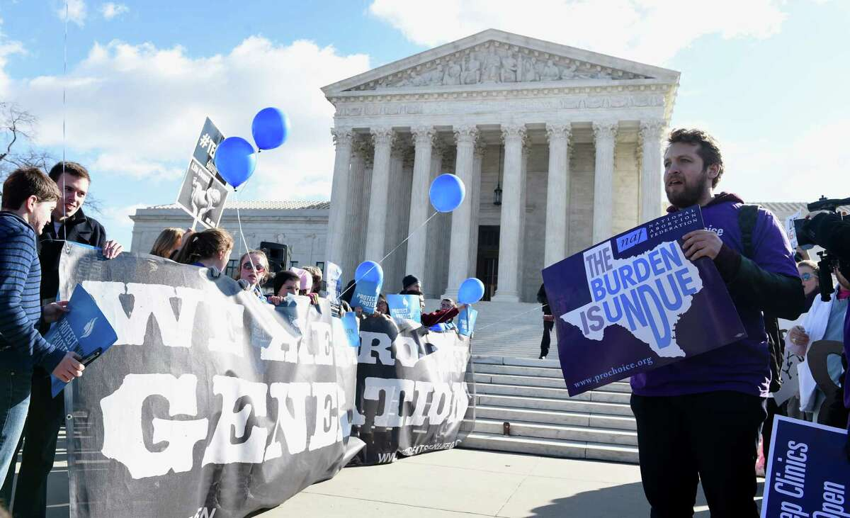 Pro-abortion rights protester Sarp Aksel of New York City, right, and anti-abortion protesters, left, rally outside the Supreme Court in Washington, Wednesday, March 2, 2016. The abortion debate is returning to the Supreme Court in the midst of a raucous presidential campaign and less than three weeks after Justice Antonin Scalia?'s death. The justices are taking up the biggest case on the topic in nearly a quarter century and considering whether a Texas law that regulates abortion clinics hampers a woman?'s constitutional right to obtain an abortion. (AP Photo/Susan Walsh) ORG XMIT: DCSW111