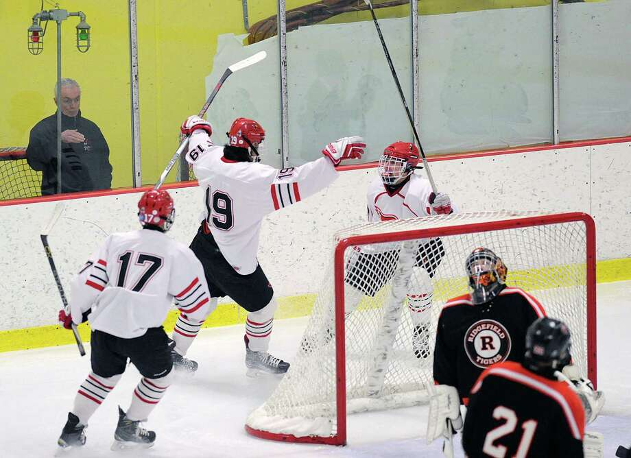 Mike Mozian (#19) of Greenwich, center, reacts after scoring the first goal of the game putting it past Ridgefield goalie Sean Keegans, foreground, during the first period of the FCIAC boys ice hockey semifinal between Ridgefield High School and Greenwich High School at Terry Connors Rink in Stamford, Conn., Wednesday, March 2, 2016. At left is Mozian's teammate Akira Dunham (#17) of Greenwich. Photo: Bob Luckey Jr. / Hearst Connecticut Media / Greenwich Time