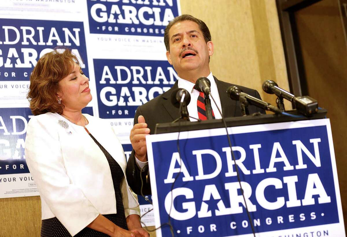 Adrian Garcia addresses his supporters with his wife, Monica, on Tuesday after he lost the Democratic congressional primary to Gene Green.