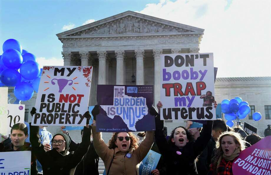 Pro-abortion rights protesters rally outside the Supreme Court in Washington, Wednesday, March 2, 2016. The abortion debate is returning to the Supreme Court in the midst of a raucous presidential campaign and less than three weeks after Justice Antonin Scalia's death. The justices are taking up the biggest case on the topic in nearly a quarter century and considering whether a Texas law that regulates abortion clinics hampers a woman's constitutional right to obtain an abortion. (AP Photo/Susan Walsh) Photo: Susan Walsh, Associated Press / AP