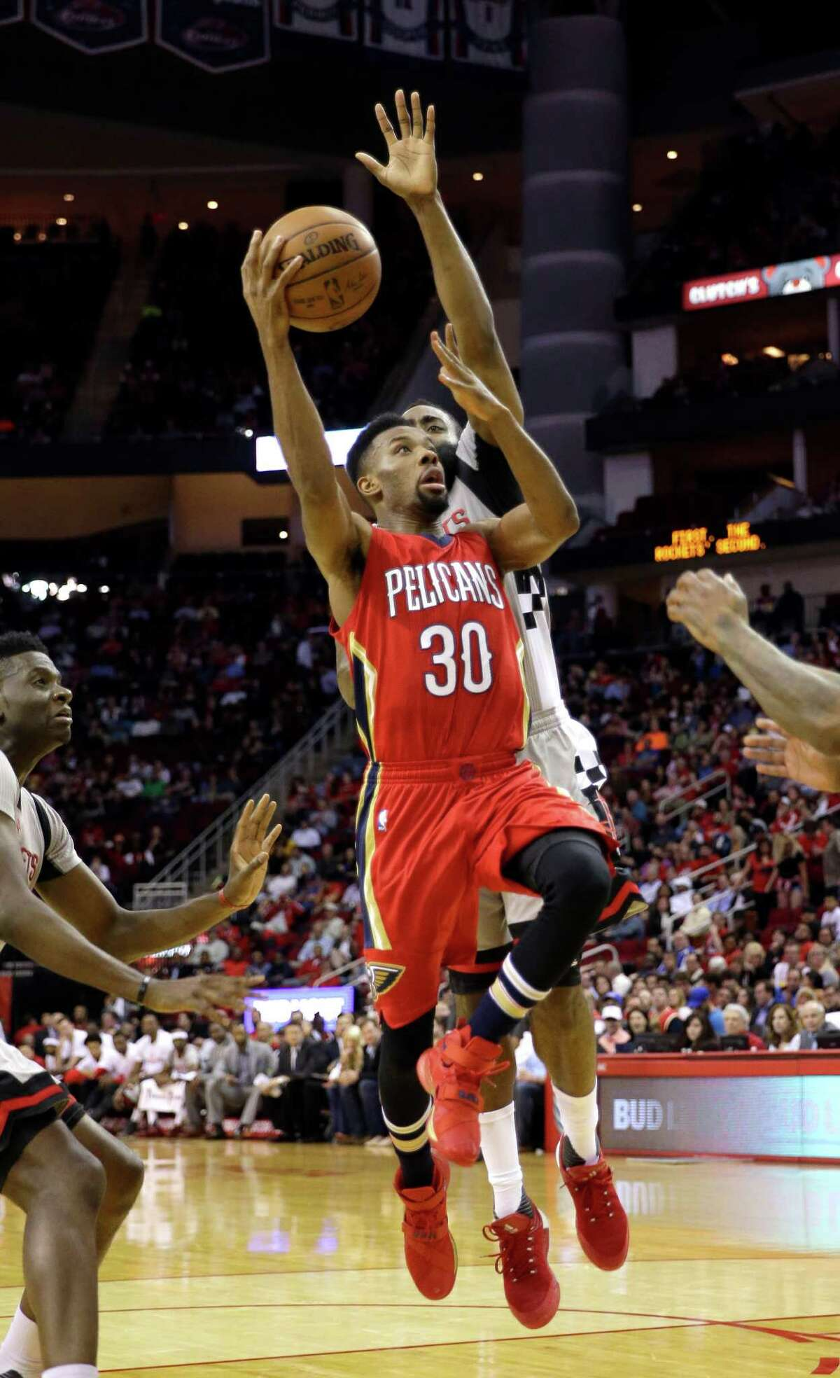 New Orleans Pelicans' Norris Cole (30) goes up for a shot as Houston Rockets' James Harden, rear, defends during the second quarter of an NBA basketball game Wednesday, March 2, 2016, in Houston. (AP Photo/David J. Phillip)