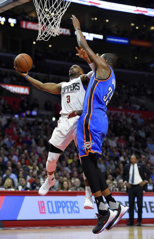 Clippers guard Chris Paul uses his left arm to fend off Thunder forward Kevin Durant as he gets to the basket. Paul scored 21 points in L.A.'s win. Photo: Mark J. Terrill, Associated Press