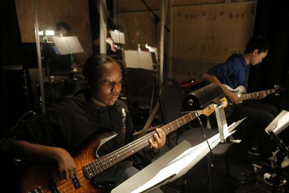 "Milenia Fountila plays bass as Kevin Xu, right, plays guitar with the pit band backstage as students from the Oakland School for the Arts performed ""School of Rock"" during a dress rehearsal at the Curran Theater in San Francisco, Calif., on Wednesday, March 2, 2016."