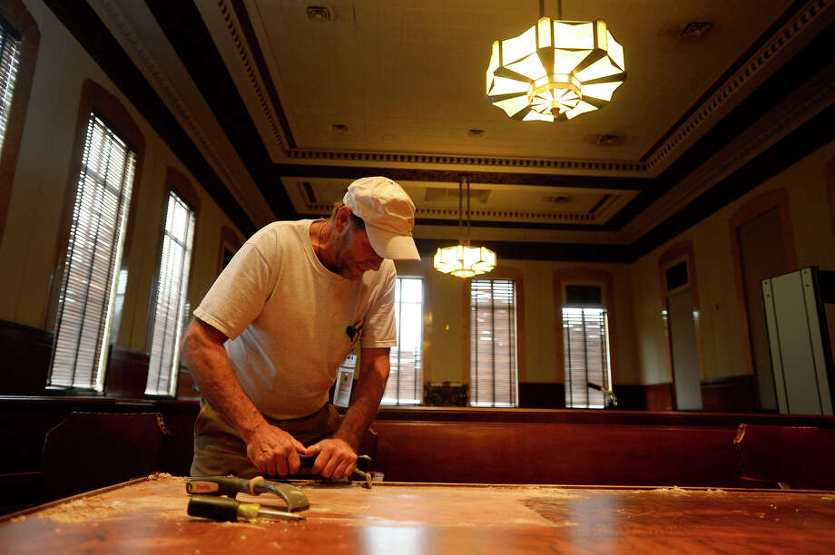 Carpenter David Weston removes the finish on a table in a courtroom at the Jefferson County courthouse on Tuesday afternoon. Two courtrooms in the old courthouse were damaged by termites.   Photo taken Tuesday 3/1/16  Ryan Pelham/The Enterprise Photo: Ryan Pelham / ©2016 The Beaumont Enterprise/Ryan Pelham