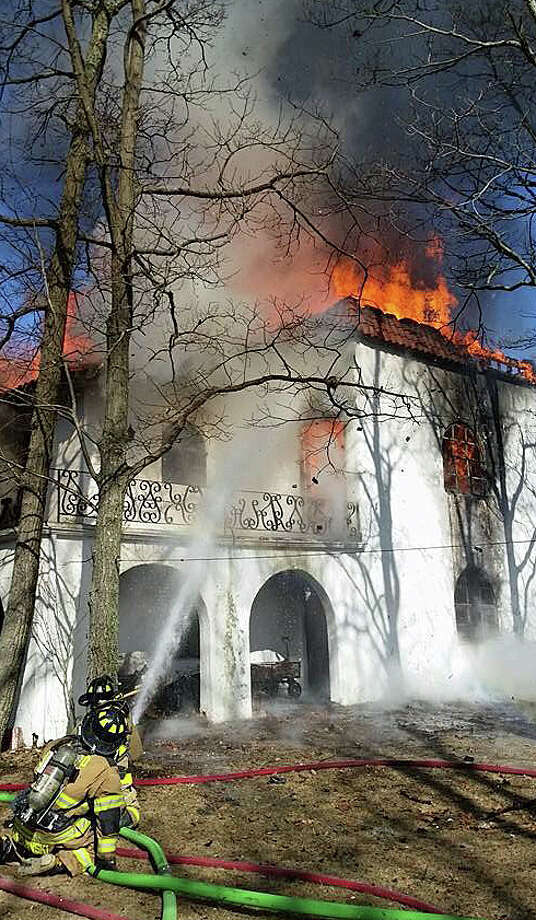 Firefighters battle a house fire on Meadow Lane in Sherman on Thursday. March 3, 2016. Fire departments from New Fairfield, Gaylordsville and Pawling, N.Y., were called for mutual aid. Photo: Contributed / Bernie Meehan