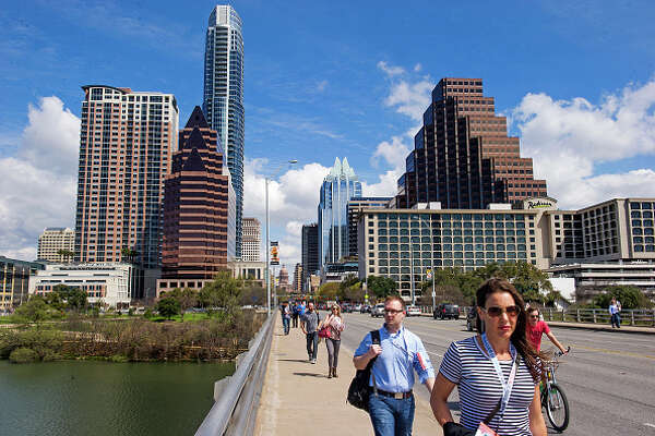 AUSTIN, TX - MARCH 13: SXSW Interactive attendees walk across the Congress Avenue Bridge in downtown Austin between SXSW events on March 13, 2015 in Austin, Texas.