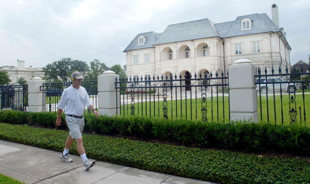 A man walks past a home in the River Oaks neighborhood.