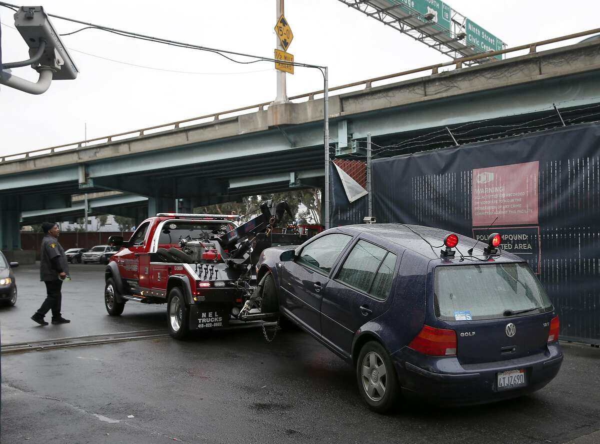 A tow truck with a car hooked to it arrives at the authorized vehicle impound lot in San Francisco, Calif. on Thursday, March 3, 2016. San Francisco has among the highest towing fees in the nation, typically running around $500 not including the cost of the parking violation.