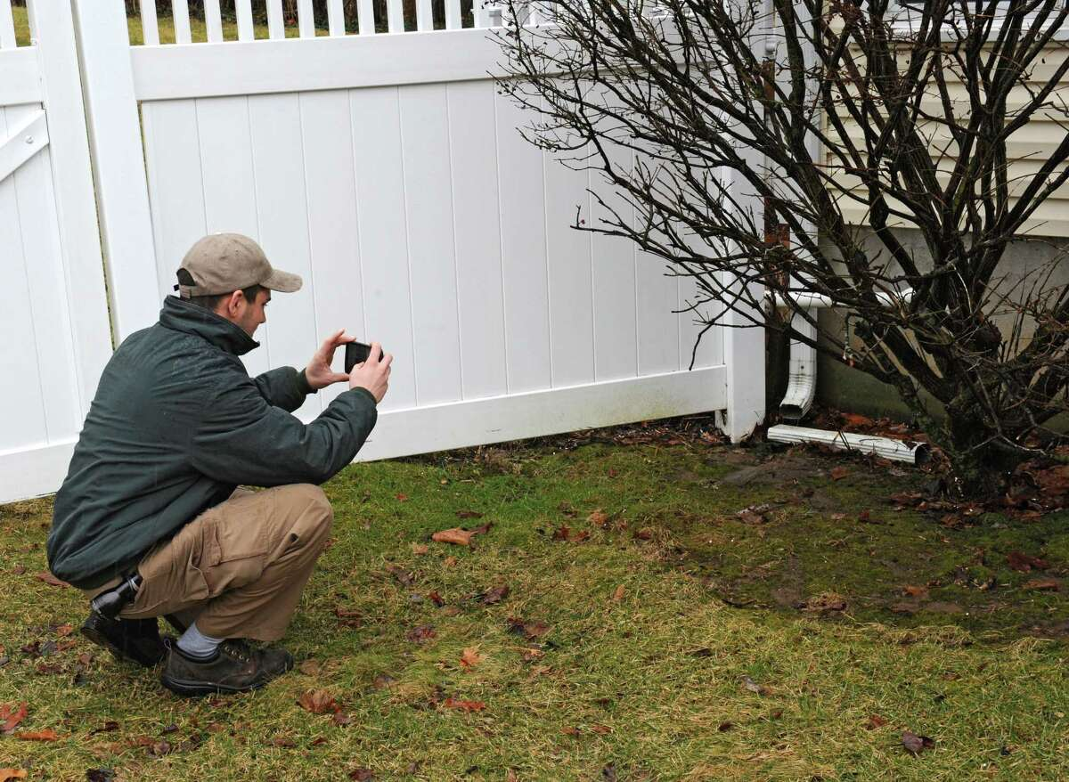 Home inspector Ryan Bergami takes a photo of a gutter spout outside a home on Thursday, Feb. 25, 2016 in Waterford, N.Y. (Lori Van Buren / Times Union)