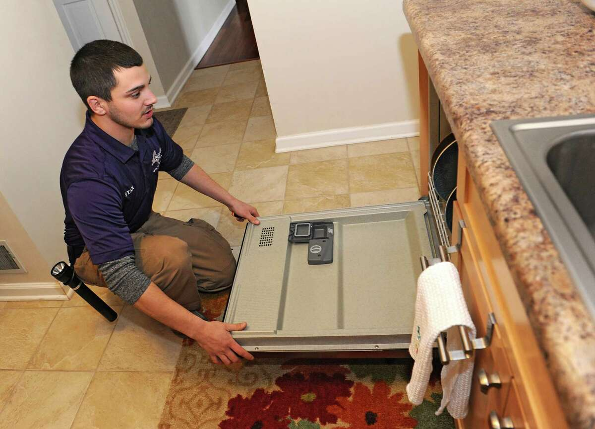Home inspector Ryan Bergami checks the door of a dishwasher in a home on Thursday, Feb. 25, 2016 in Waterford, N.Y. (Lori Van Buren / Times Union)