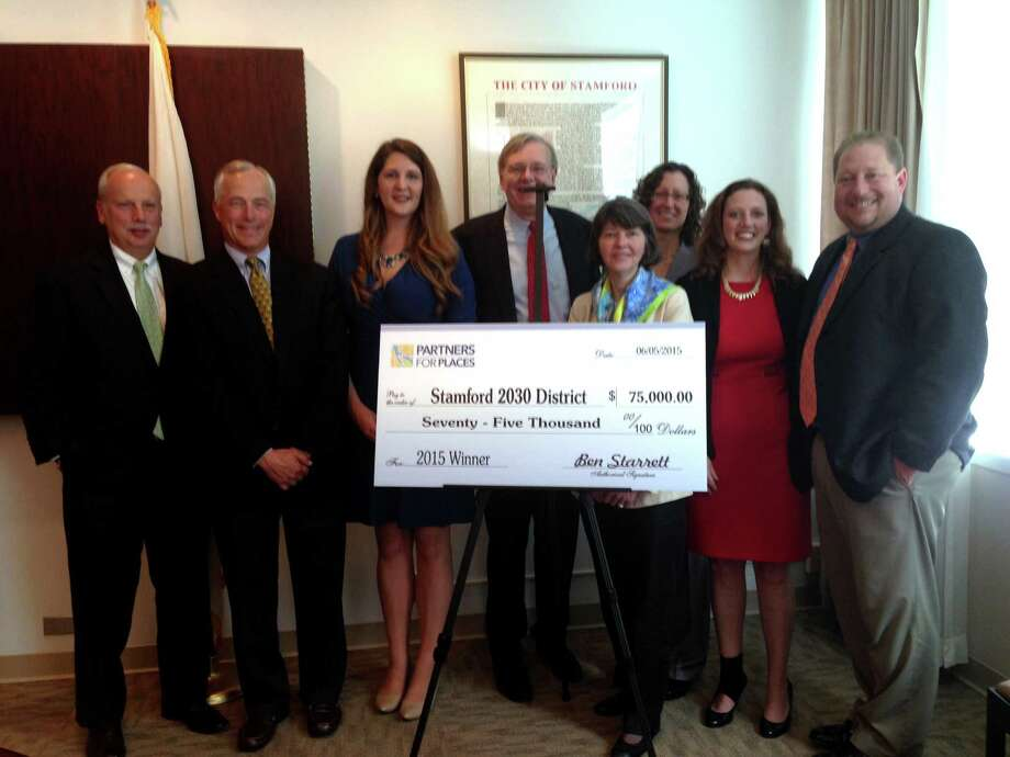 The Stamford 2030 District is awarded a grant from the Funders' Network for Smart Growth and Livable Communities. From left to right: Rey Giallongo, CEO of the First County Bank, Hank Ashforth, of The Ashforth Company, Megan Saunders, executive director of the Stamford 2030 District, Mayor David Martin, Anne Wallace, director of programs at the Funders' Network, Michelle Knapik, president of the Emily Hall Tremaine Foundation, Andrea Pinabell, vice president of sustainability for Starwood H-tels and Resorts, and Thomas Madden, the city's economic development director. Photo: Keila Torres Ocasio / Staff Photo / Stamford Advocate