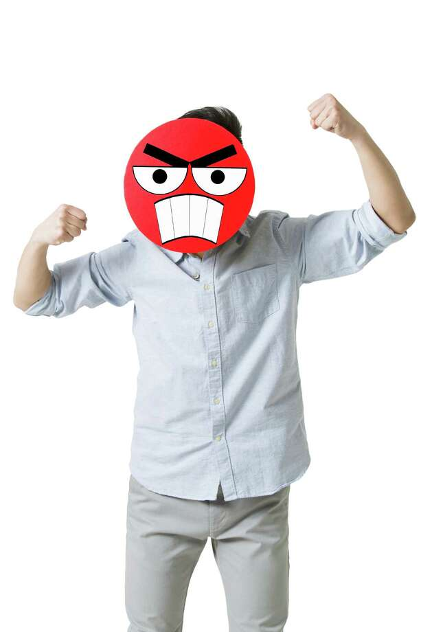 Young man with a angry emoticon face in front of his face Photo: BJI / Blue Jean Images, Getty Images / blue jean images RF
