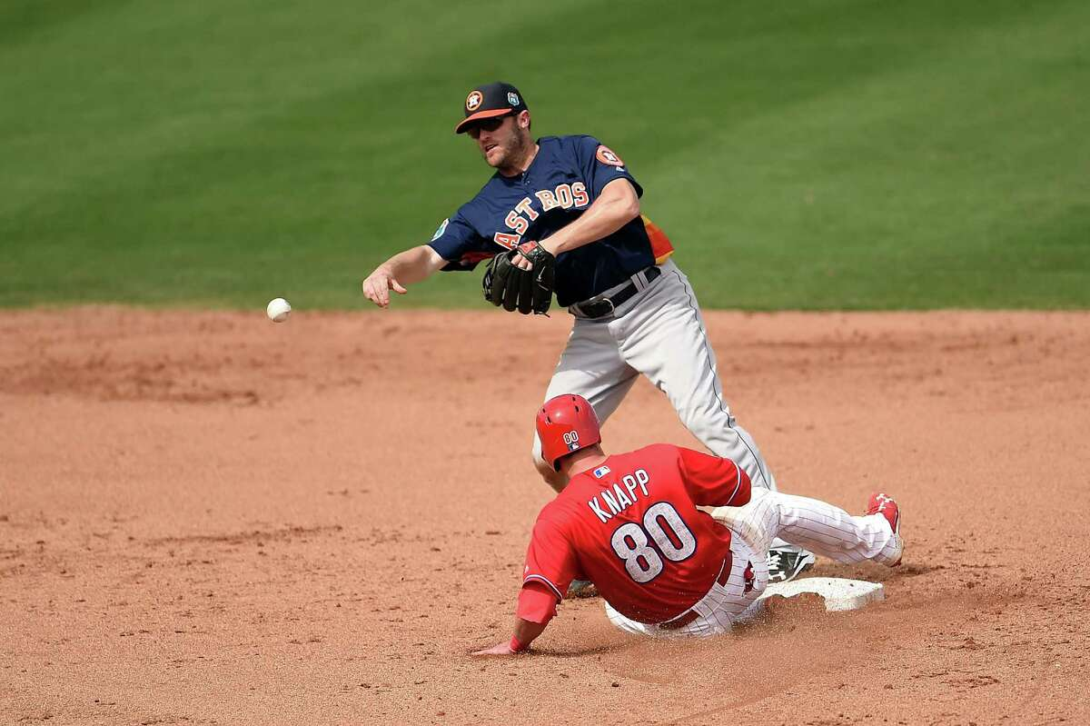CLEARWATER, FL - MARCH 03: Danny Worth #26 of the Houston Astros makes a throw to first base as Andrew Knapp #80 of the Philadelphia Phillies slides into second base during the third inning of a spring training game at Bright House Field on March 3, 2016 in Clearwater, Florida.