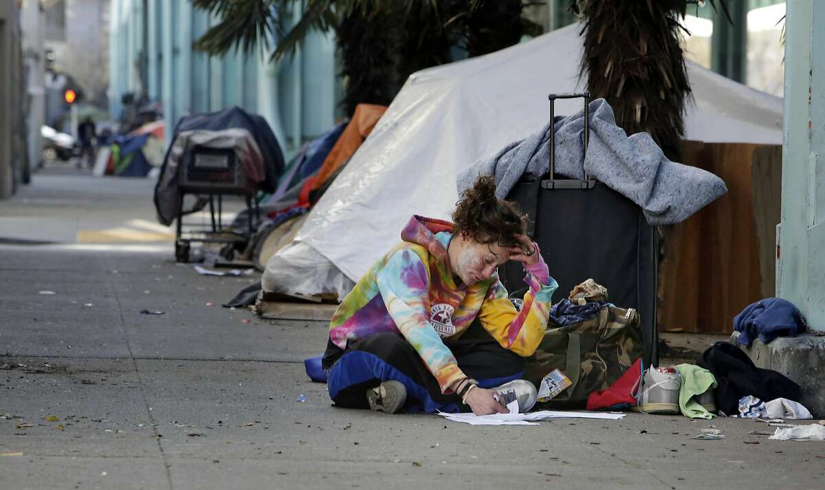 Emma Mason, who is a homeless resident in the area, writes on paper underneath an Abatement Order to Vacate to homeless encampment tent owners on a pillar along 13th Street on Wednesday, February 24, 2016 in San Francisco, California.