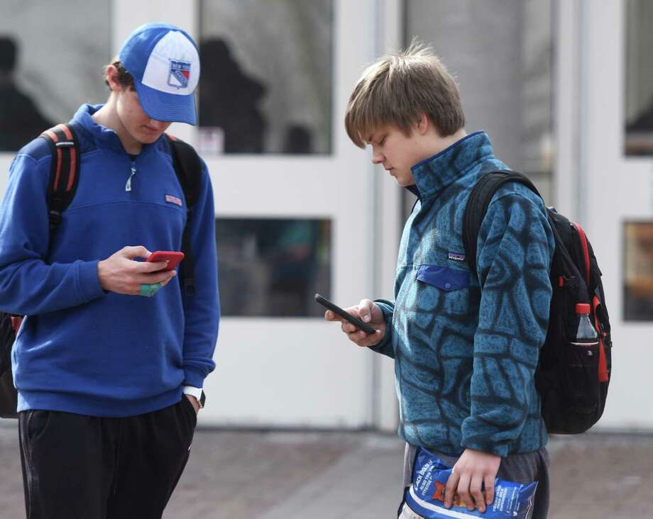 "Greenwich High School sophomore Ashton Greschner, left, and junior Brian Vezina use their cellphones after school in the school courtyard on Thursday. Vezina admits that he is always on his phone, even in class, but says he uses it for school research too. ""Like Snapchat?"" said his friend, Greschner. Photo: Tyler Sizemore / Hearst Connecticut Media / Greenwich Time"