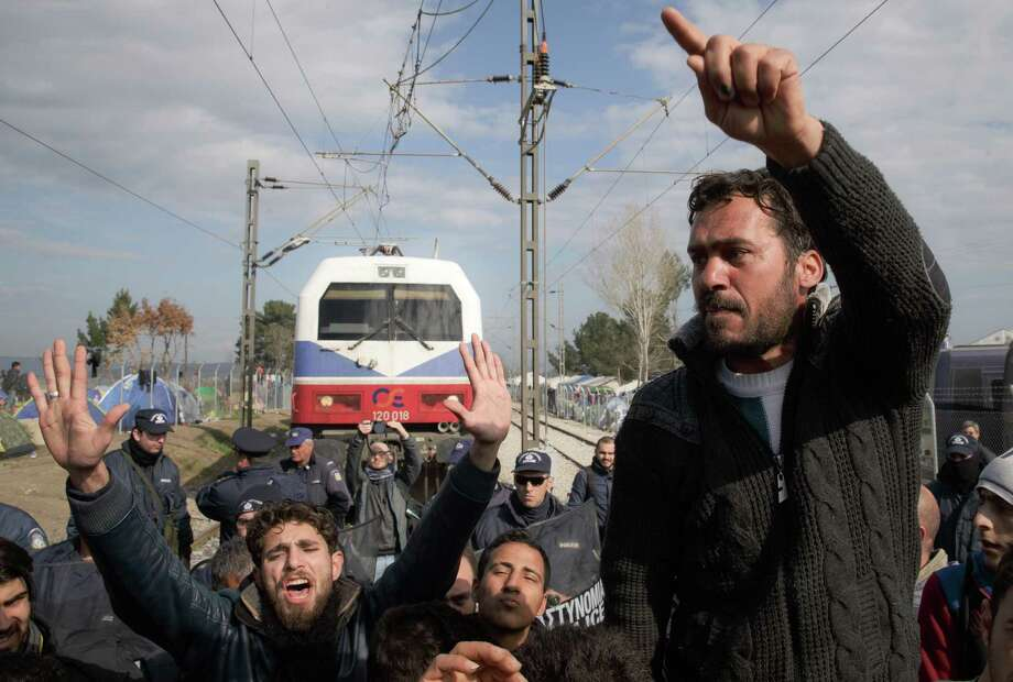 Migrants shout slogans while blocking a railway during the protest demanding the opening of the border between Greece and Macedonia in the northern Greek border station of Idomeni, Thursday, March 3, 2016. Thousands of refugees and migrants wait on the border between Greece and Macedonia and about 30,000 refugees and other migrants are stranded in Greece, with 10,000 at the Idomeni border crossing to Macedonia. (AP Photo/Vadim Ghirda) Photo: Vadim Ghirda, STF / AP