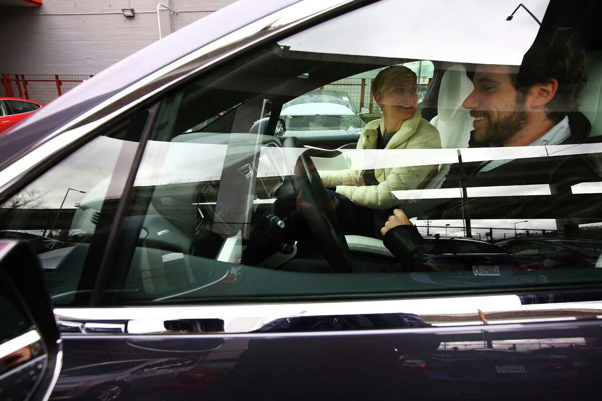 Justin and Kat Speyer test drive the new Tesla Model X at a private event at Tesla's Sodo service center, Thursday, March 3, 2016. Though the electric car's base model is set to start at $75,000, the first 1,000 Model Xs are fully-loaded signature series P90D versions that go for around $132,000.