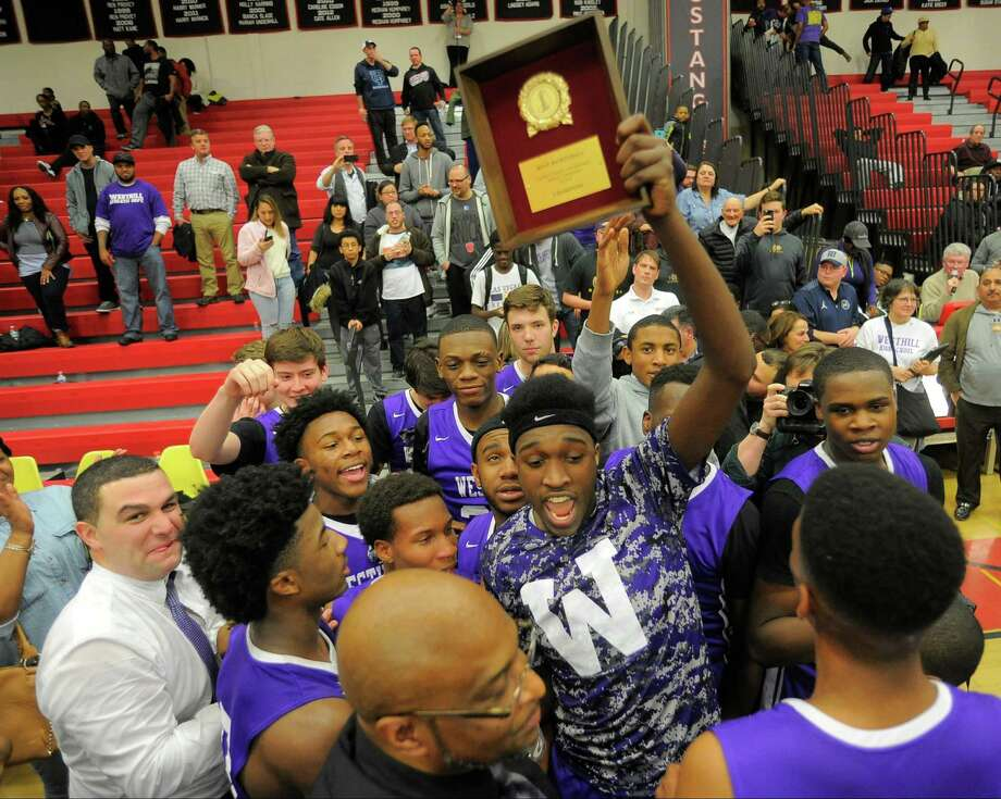 Westhill Lenold August holds the championship plaque as his team celebrates their win over Danbury. Westhill defeated Danbury 72-61 in an FCIAC basketball championship at Fairfield Warde High School in Fairfield, Conn. on  March 3, 2016. Photo: Matthew Brown, Hearst Connecticut Media / Stamford Advocate