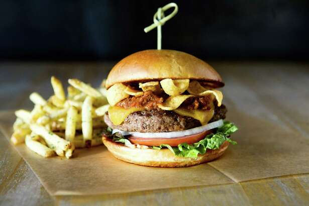 "Hopdoddy Burger Bar of Austin will open a new Houston restaurant in April at River Oaks District, Houston. Shown here: the Terlingua burger with chile con carne, cheddar, Fritos and ""sassy sauce."""