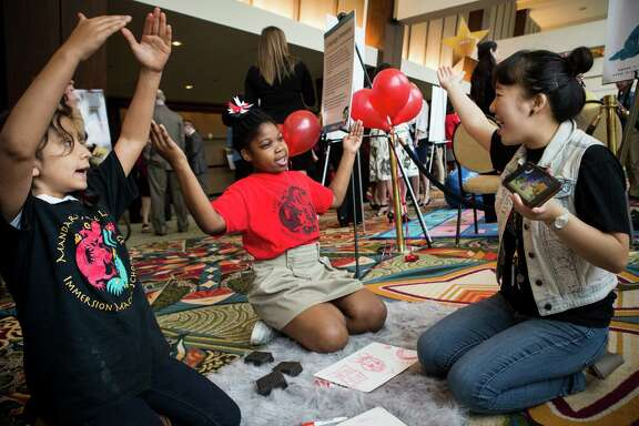 Yabei Yin, second grade teacher at Mandarin Chinese Language Immersion Magnet School, right, gives a language lesson demonstration with students, Senia Ziegler, left, and Promise Jackson, outside the Houston Independent School District's State of The Schools event on Thursday, March 3, 2016, in Houston.