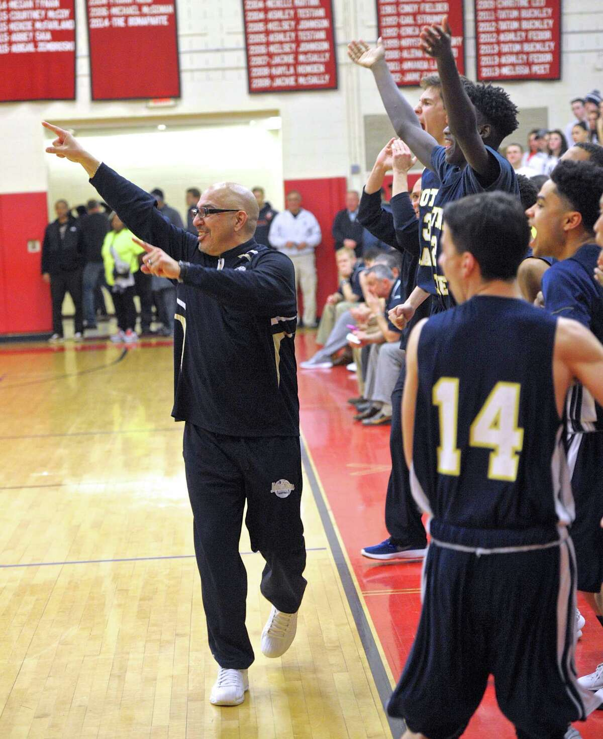 Coach Vin Laczkoski, back following a four-game suspension, begins the celebration on the Notre Dame-Fairfield be nch in the closing seconds of the Lancers' 76-64 win over Immaculate in the SWC final Thursday night at Masuk.