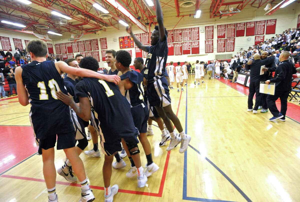 Notre Dame-Fairfield players and coaches celebrate their victory in the SWC boys basketball championship gam between Immaculate and Notre Dame-Fairfield high schools on Thursday night March 3, 2016, at Masuk High School, Monroe, Conn.