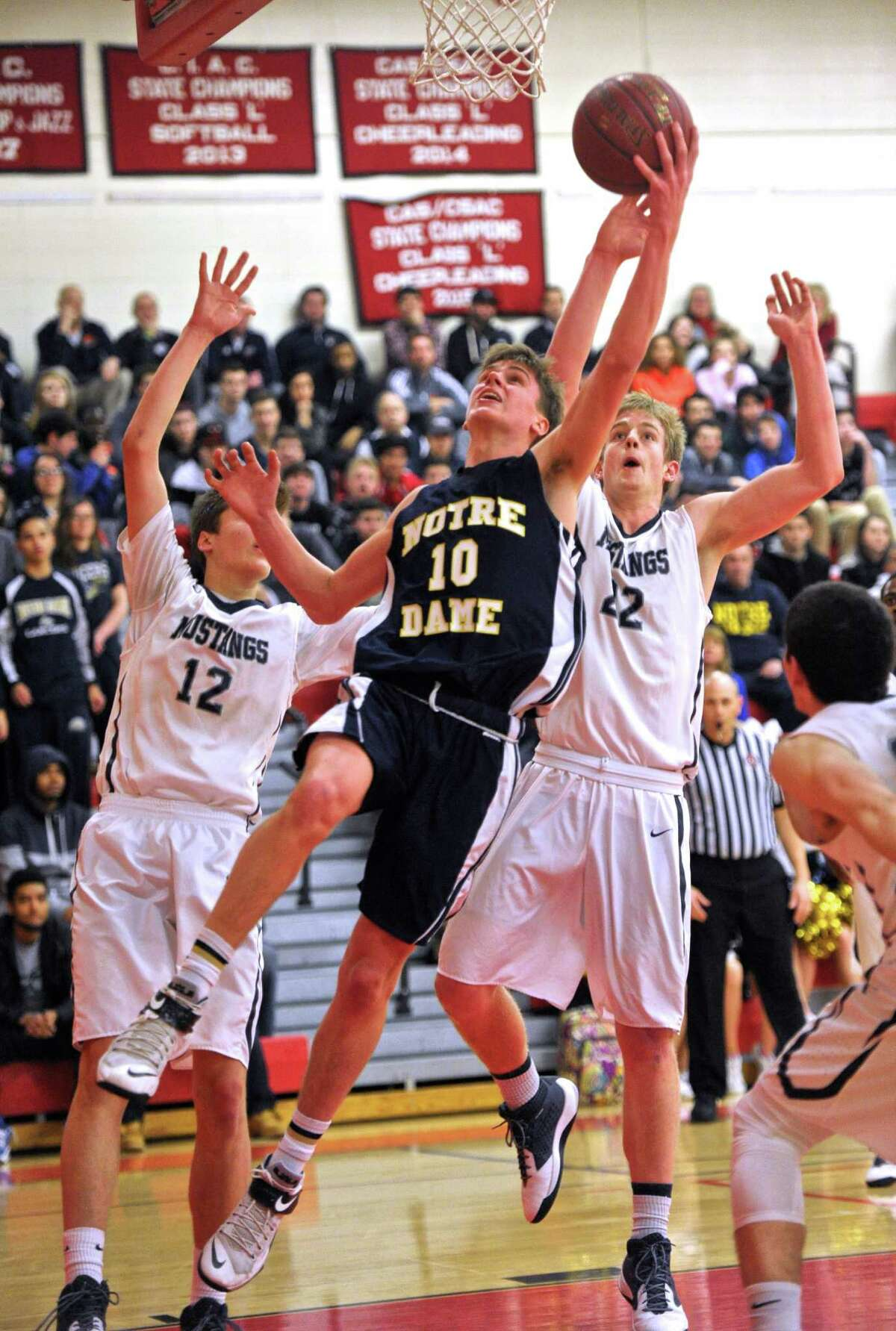 Notre Dame-Fairfield's Colin Burke (10) splits Immaculate's Alex Gerbo (12) and William Hatcher (22) on his way to the basket in the SWC boys basketball championship game between Immaculate and Notre Dame-Fairfield high schools on Thursday night March 3, 2016, at Masuk High School, Monroe, Conn.