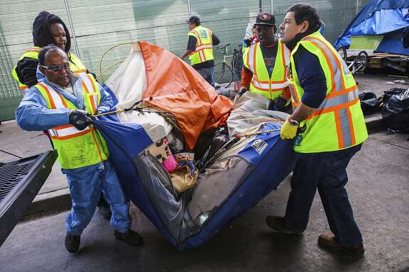 Department of Public Works employees haul an abandoned tent on Division Street in San Francisco, California, on Tuesday, March 1, 2016.