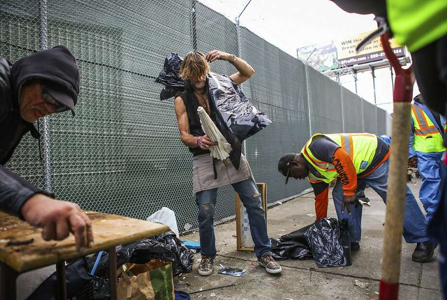 Department of Public Works employees help Mike Francis (center), a homeless man, as he collects belongings with his companion Larry Muraoka (left), before being forced to move from Division Street, in San Francisco, California, on Tuesday, March 1, 2016. Photo: Gabrielle Lurie, Special To The Chronicle