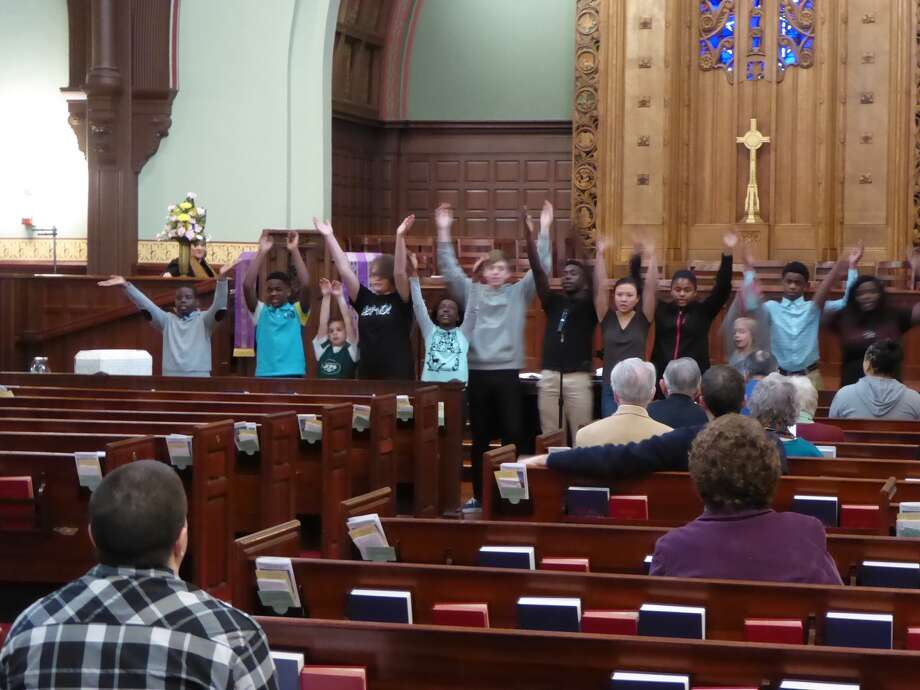 """The dozen cast members of an original rap/hip hop musical, """"Speak Loud, Speak Proud,"""" ranging in age from 6 to 18, rehearse their rendition of ?Glory? at a service at First Presbyterian Church. The song from the film """"Selma"""" is featured in the new musical co-directed by Guilderland High School senior Katie Lamar. The full show with spoken-word monologues and four songs by the cast in costume will be at 12:15 p.m. Sunday, at the church, 362 State St., Albany. (Photo by Richard Gascoyne)"""