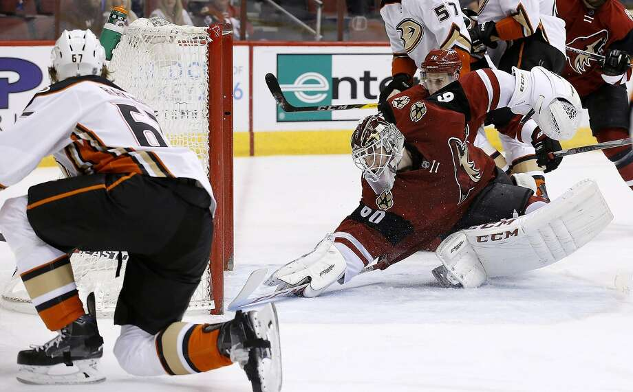 Anaheim Ducks' Rickard Rakell (67), of Sweden, sends the puck past Arizona Coyotes' Niklas Treutle, right, of Germany, for a goal during the first period of an NHL hockey game Thursday, March 3, 2016, in Glendale, Ariz. (AP Photo/Ross D. Franklin) Photo: Ross D. Franklin, AP