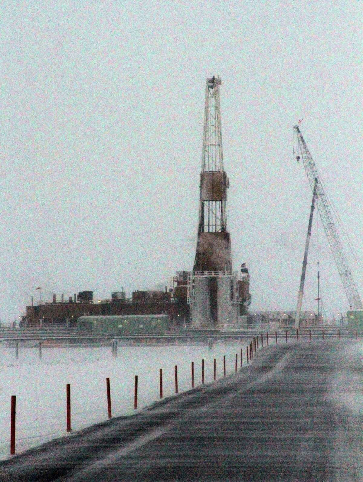 This Feb. 9, 2016, photo shows a million-pound drilling rig looming in the distance at the CD5 drilling site on Alaska's North Slope. ConocoPhillips in October 2015 became the first to drill for oil in the National Petroleum Reserve-Alaska, a region the size of Indiana set aside by President Warren G. Harding in 1923. (AP Photo/Mark Thiessen)