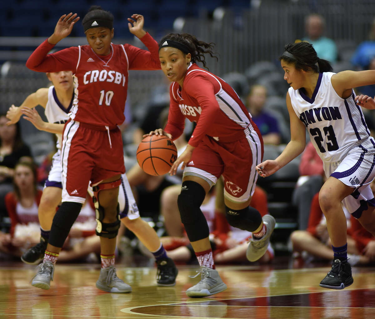 Crosby sophomore guard Paris Netherly leads a fast break against Canyon junior guard Angel Hayden (23) in the fourth quarter of their Class 5A girls basketball state semifinal at the Alamodome in San Antonio on Thursday, Mar. 3, 2016. (Photo by Jerry Baker/Freelance)