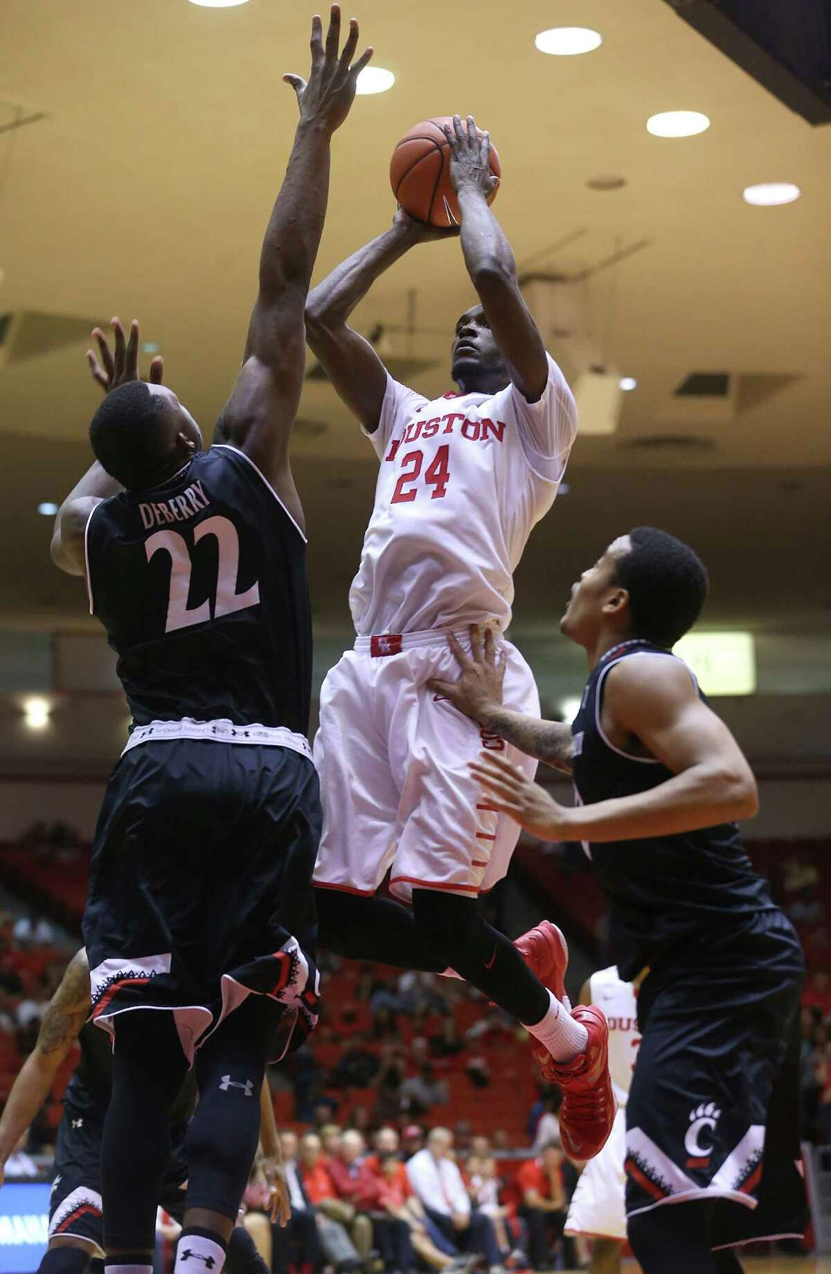Houston Cougars forward Devonta Pollard (24) puts up two of his 11 points against Cincinnati Bearcats center Coreontae DeBerry (22) at Hofheinz Pavilion on Thursday, March 3, 2016, in Houston. Cougars won 69-56.