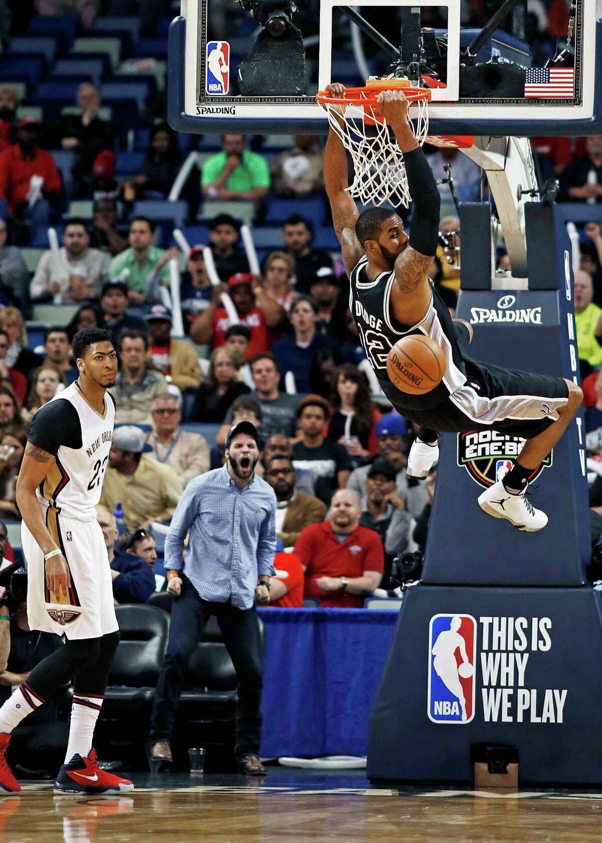 San Antonio Spurs forward LaMarcus Aldridge (12) dunks as New Orleans Pelicans forward Anthony Davis watches during the first half of an NBA basketball game in New Orleans, Thursday, March 3, 2016. (AP Photo/Max Becherer)