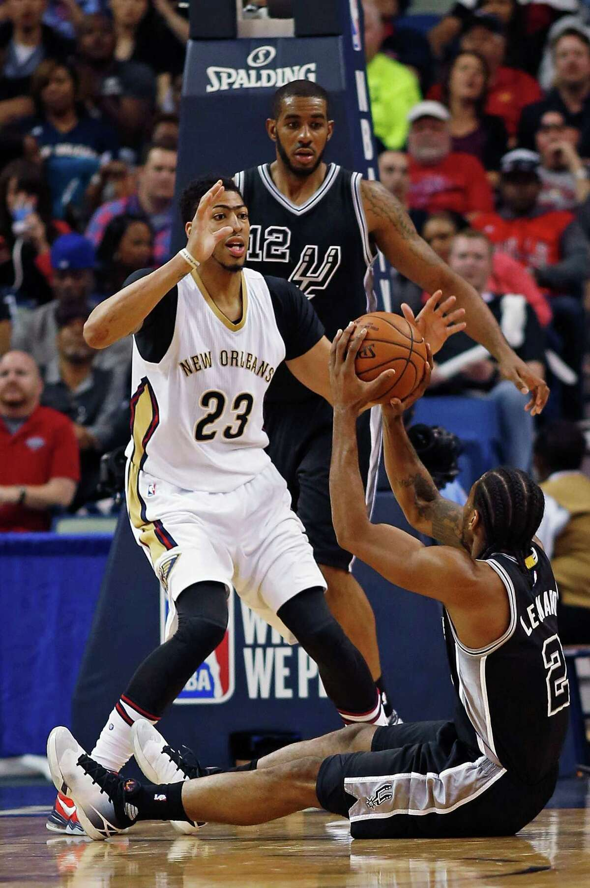 San Antonio Spurs forward Kawhi Leonard (2) attempts to pass from the ground against New Orleans Pelicans forward Anthony Davis during the first half of an NBA basketball game in New Orleans, Thursday, March 3, 2016. (AP Photo/Max Becherer)