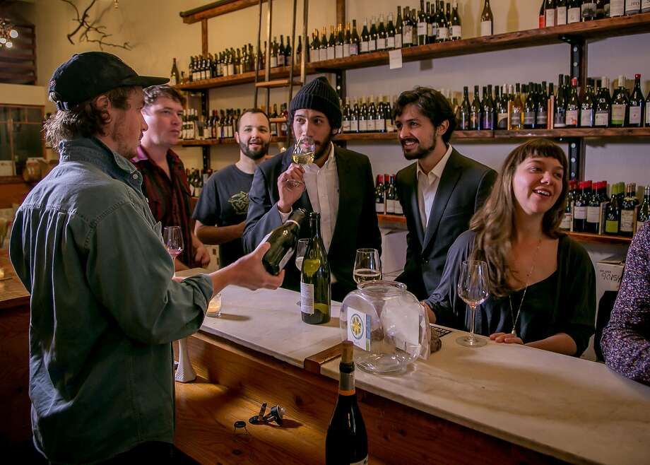 Ordinaire owner Bradford Taylor (left) pours at the Oakland wine bar, which has an extensive selection of natural wines — unfiltered, idiosyncratic and a bit funky. Photo: John Storey, Special To The Chronicle
