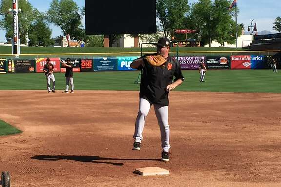 Will Clark, a special camp instructor, fields throws at first base during a drill at Scottsdale Stadium on Friday.