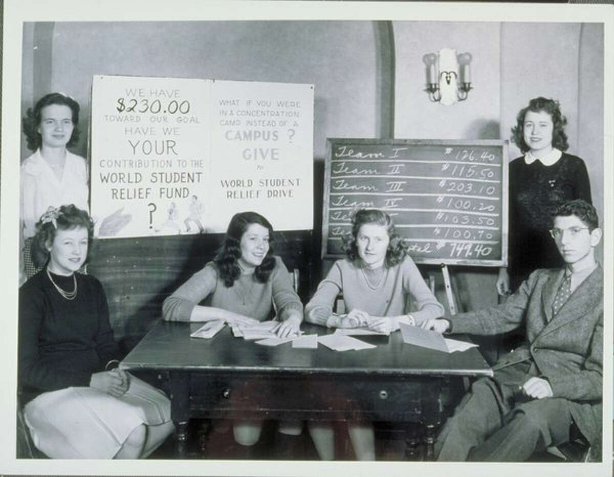 World Student Relief Drive, 1939-1945. Five women and one man seated or standing next to a table, poster and blackboard. Poster solicits contributions for the World Student Relief Drive. Team totals for contributions shown on blackboard.
