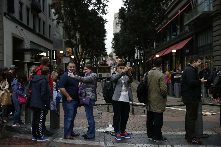 Visitors take selfies while lined up waiting for a cable car on Powell Street. Photo: Leah Millis Leah Millis, The Chronicle